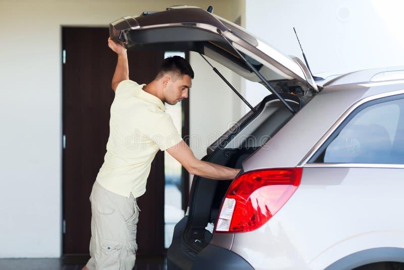 Homem novo com o tronco de carro aberto no lugar de estacionamento imagem de stock royalty free