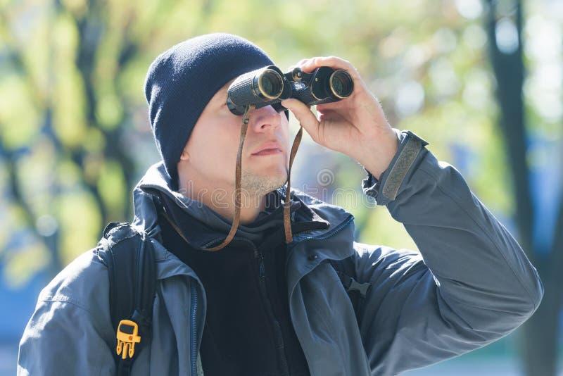 Homem novo com a ornitologia dos binóculos no fundo natural da demi-estação fotos de stock