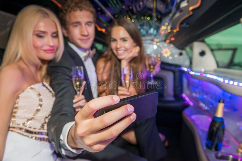 Homem novo com os amigos fêmeas que tomam o selfie no telefone celular em l imagens de stock