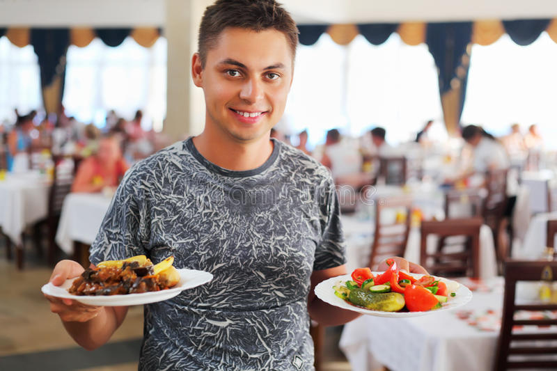 Homem novo com os dois pratos nas mãos no restaurante imagem de stock