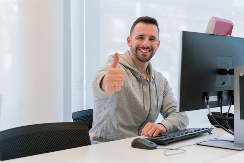 Homem novo com os polegares acima de feliz e do sorriso para ter conseguido seus objetivos no escritório na frente do computador fotos de stock