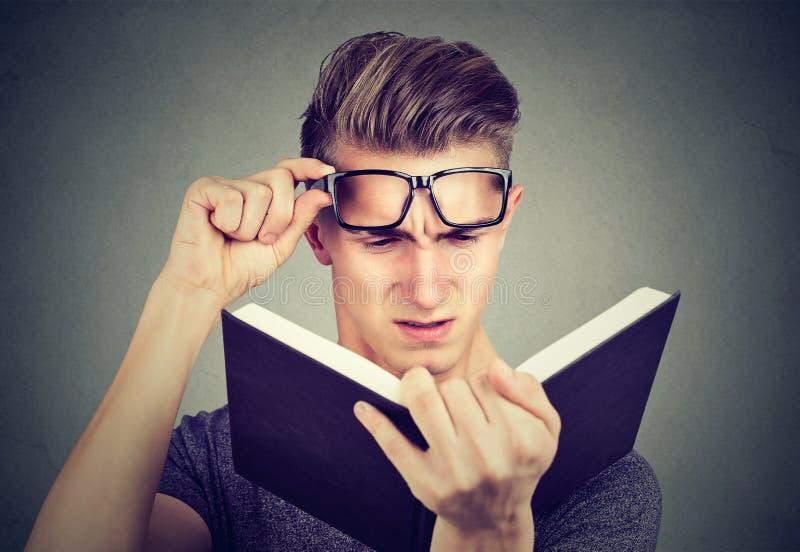 Homem novo com os vidros que sofrem da fadiga ocular que lê um livro que tem problemas da visão foto de stock royalty free