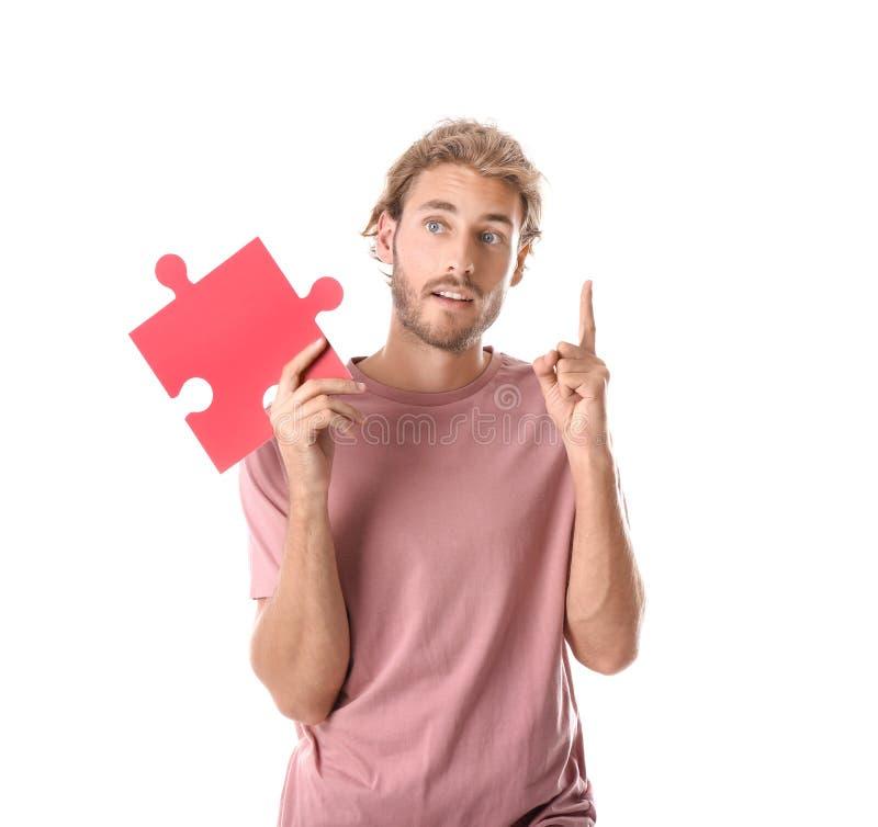 Homem novo com parte de enigma de serra de vaivém e o indicador aumentado no fundo branco fotos de stock royalty free