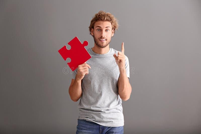 Homem novo com parte de enigma de serra de vaivém e o indicador aumentado no fundo cinzento imagens de stock royalty free