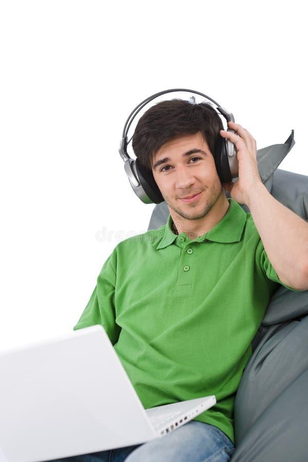 Homem novo com portátil e auscultadores imagens de stock