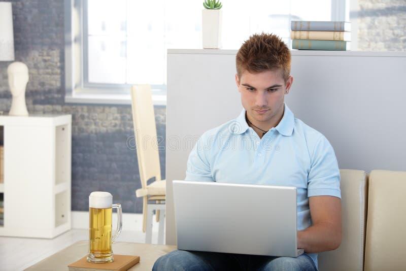 Homem novo com portátil e cerveja fotografia de stock royalty free