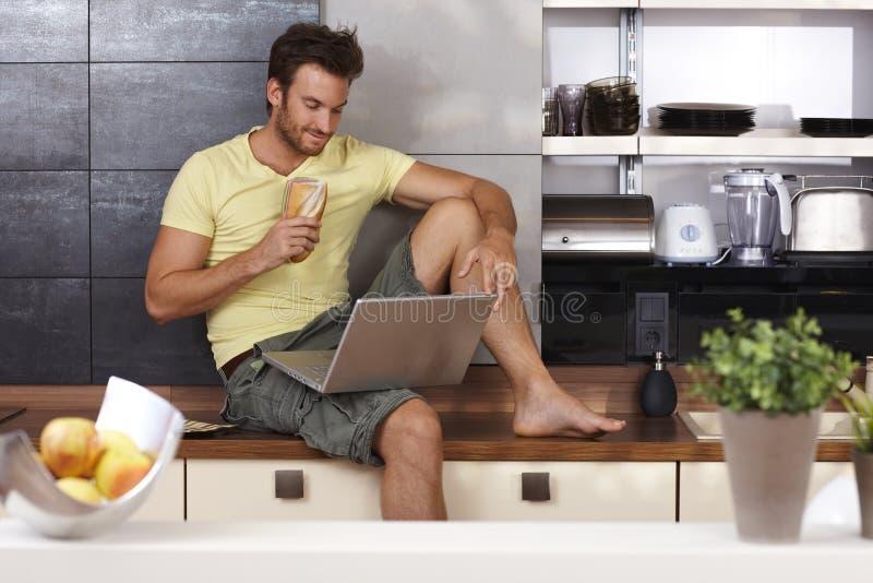 Homem novo com portátil e sanduíche imagens de stock