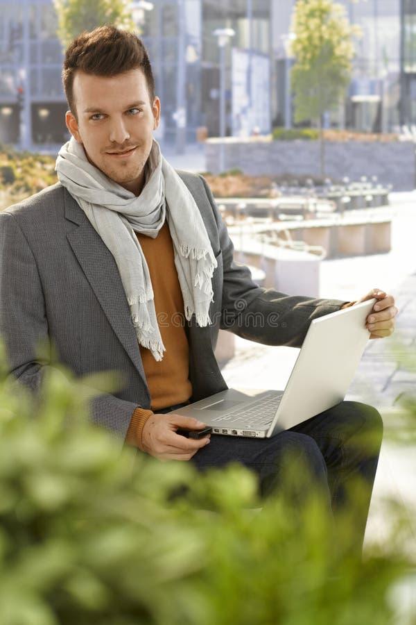 Homem novo com portátil fora fotos de stock royalty free