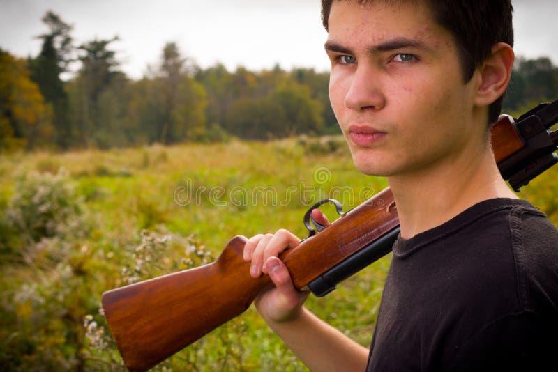 Homem novo com rifle imagem de stock royalty free