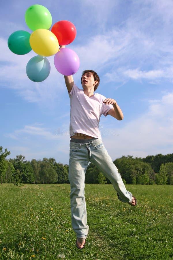 Homem novo com salto colorido de muitos balões imagens de stock royalty free
