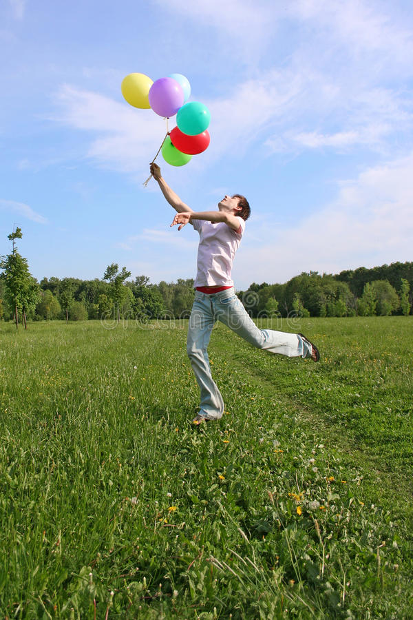 Homem novo com salto colorido de muitos balões fotos de stock royalty free