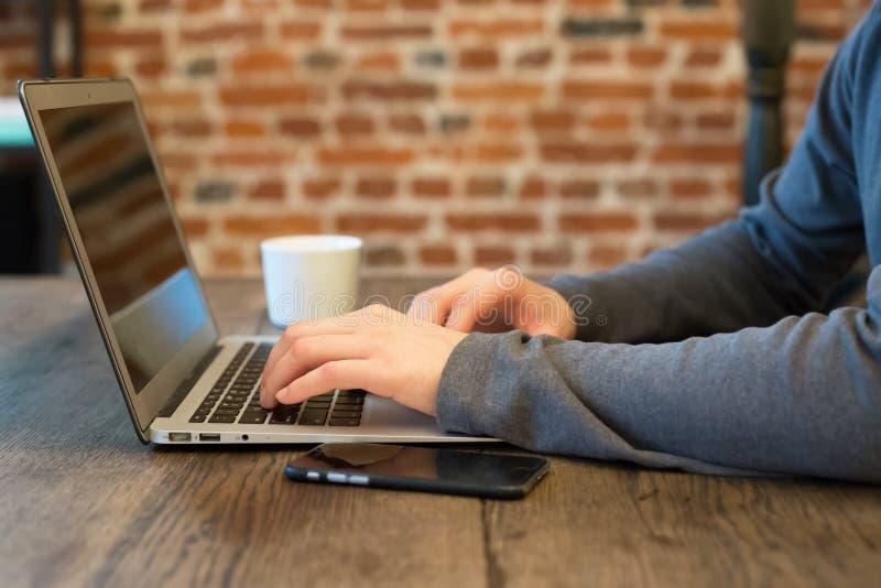 Homem novo com seu portátil na sala Procurarando o Web fotos de stock royalty free