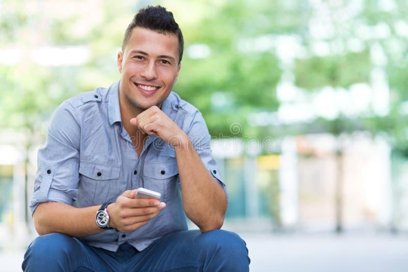 Homem novo com smartphone fotos de stock