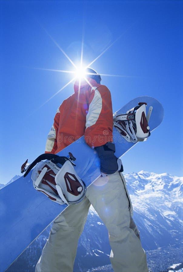 Homem novo com snowboard foto de stock