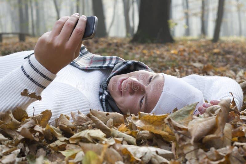 Homem novo com sorriso e telefone de mobil no autumun imagem de stock royalty free