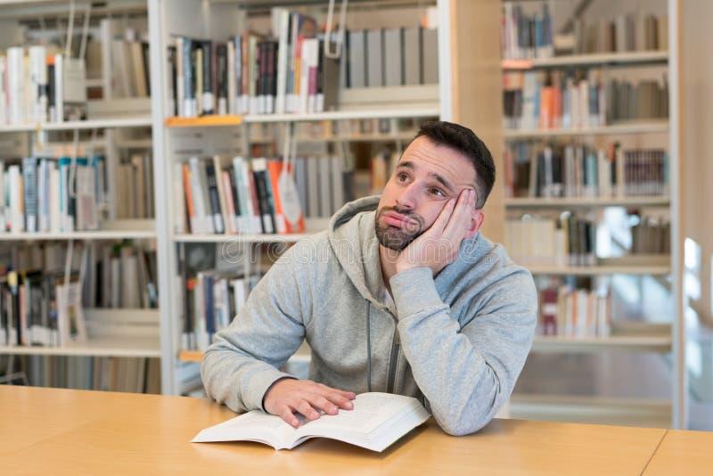 Homem novo com sua cabeça que descansa em sua mão cansado e furada de ler um livro na biblioteca foto de stock royalty free