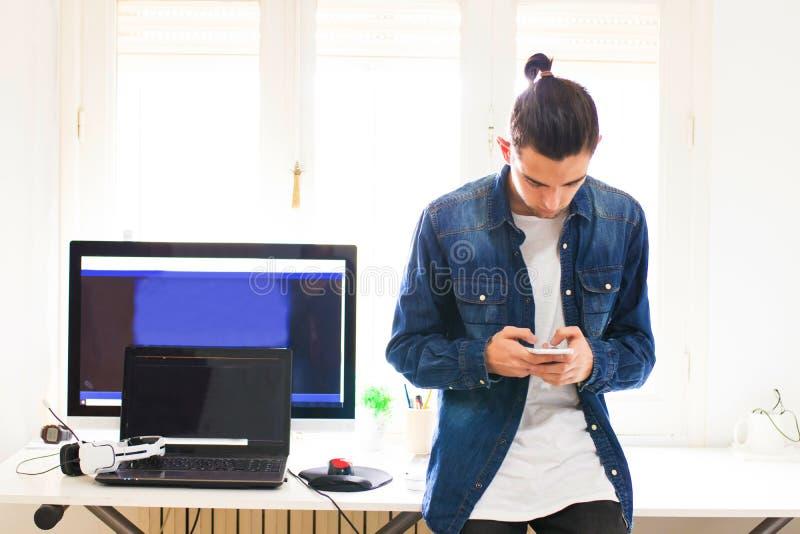 Homem novo com telefone celular e computador imagens de stock