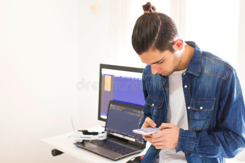 Homem novo com telefone celular e computador foto de stock