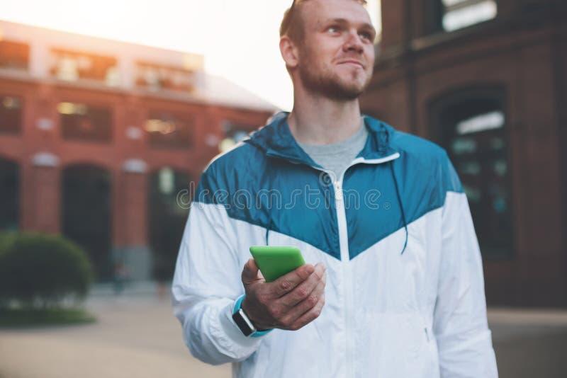 Homem novo com telefone celular em sua mão que está na rua e no sorriso foto de stock royalty free