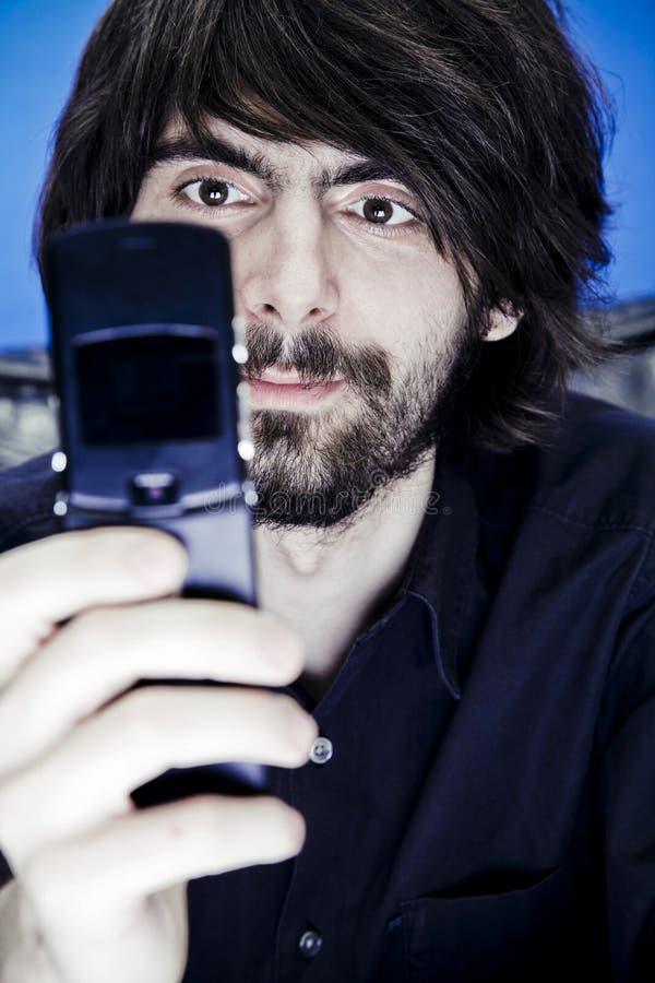 Homem novo com telefone da câmera fotografia de stock royalty free