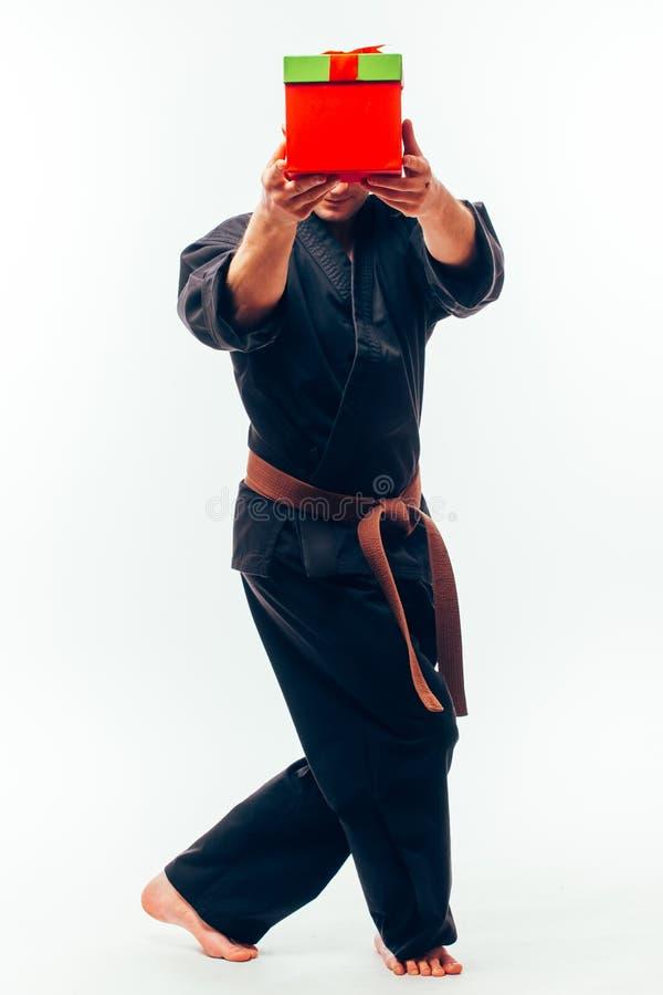Homem novo com treinamento alaranjado do lutador do karaté da correia com caixa de presente fotografia de stock royalty free