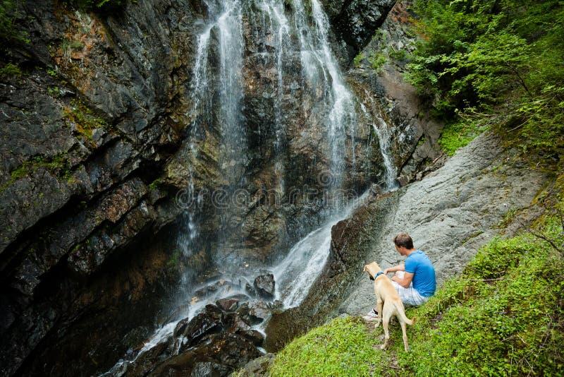 Homem novo com um cão perto de uma cachoeira imagens de stock