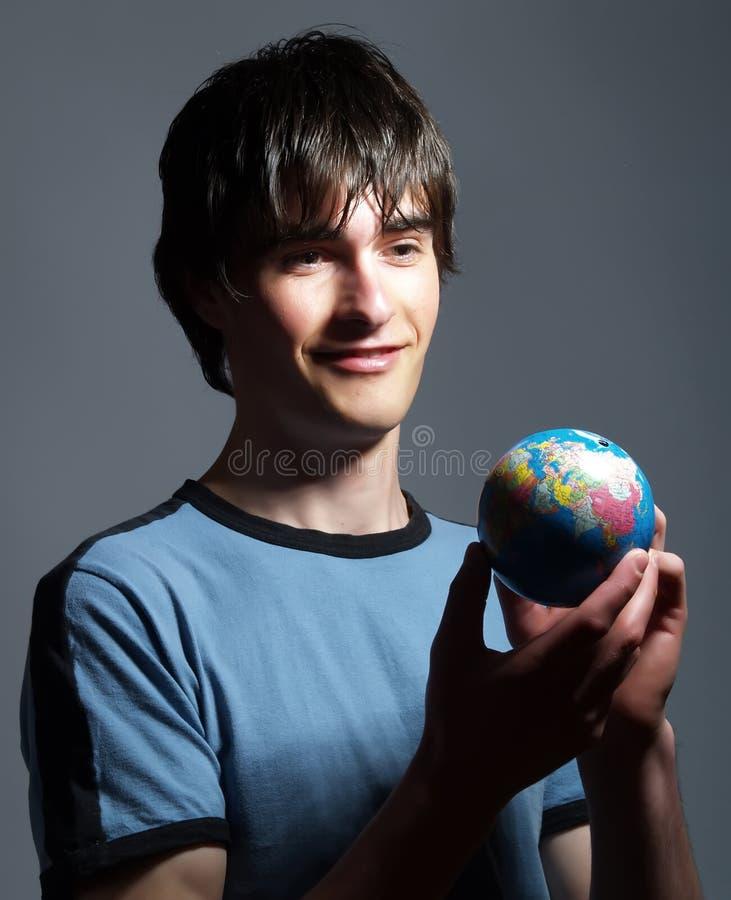 Homem novo com um globo fotografia de stock