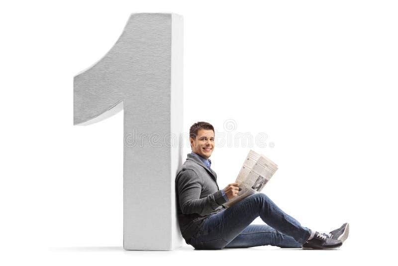 Homem novo com um jornal que inclina-se contra um número do cartão sobre fotografia de stock royalty free