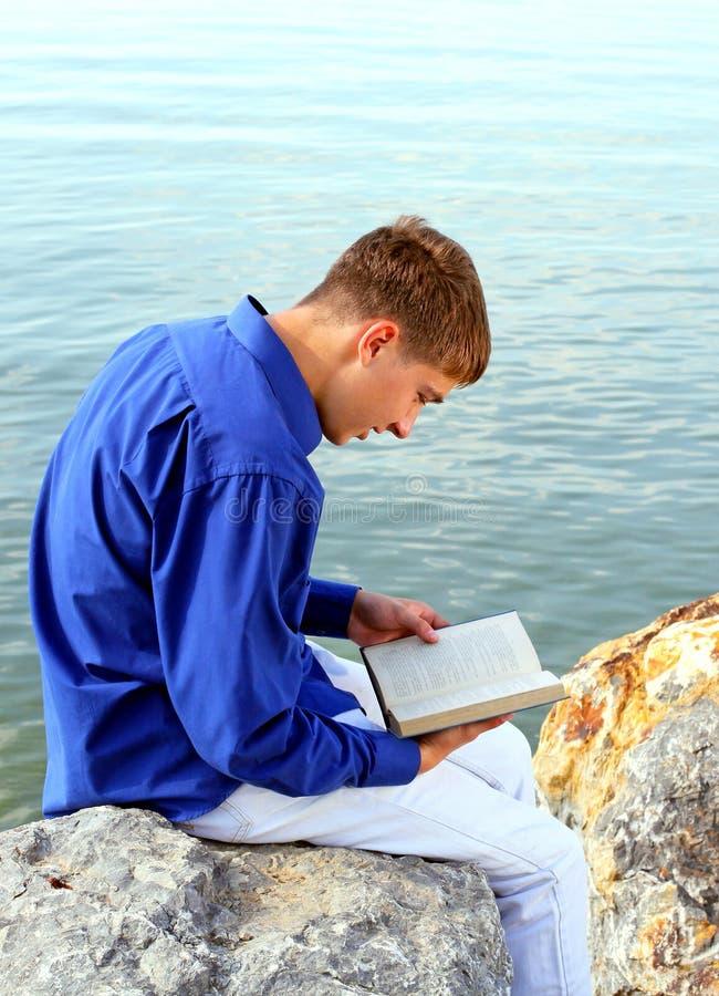 Homem novo com um livro exterior fotografia de stock royalty free