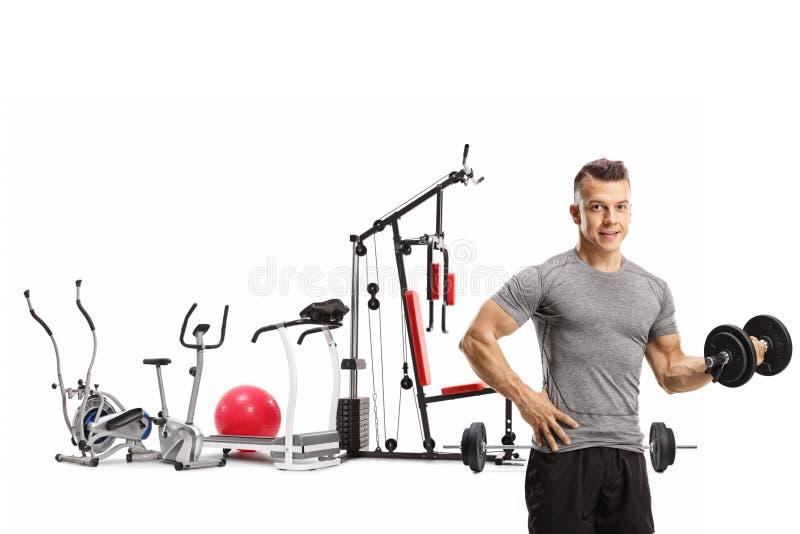 Homem novo com um peso e umas m?quinas de exerc?cio diferentes da aptid?o fotografia de stock