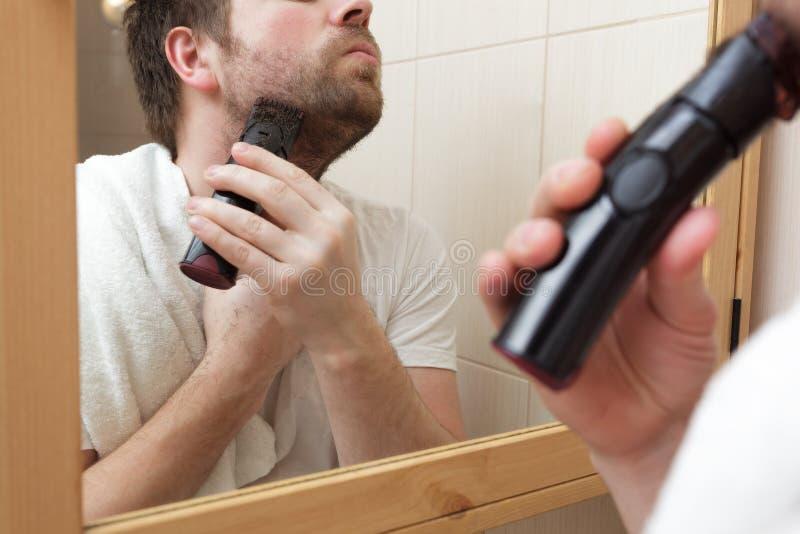Homem novo com um restolho da barbeação da barba com lâmina elétrica foto de stock royalty free