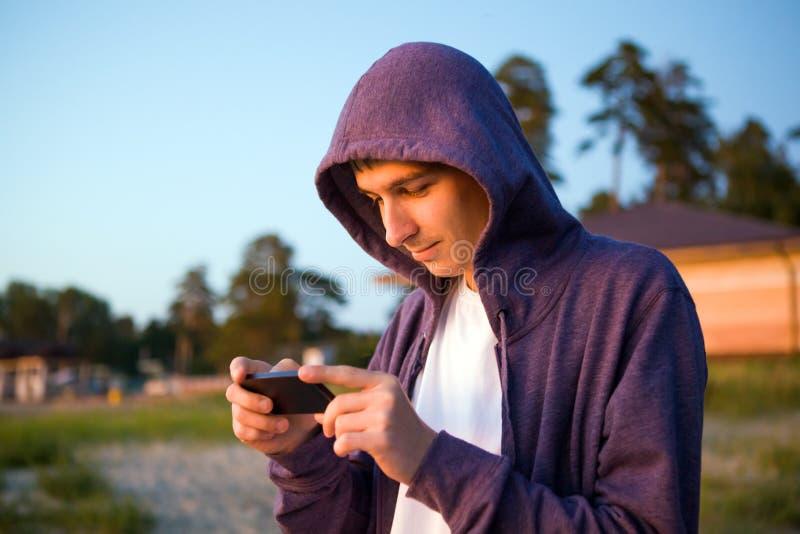 Homem novo com um telefone fotos de stock