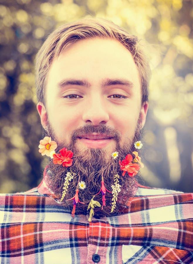 Homem novo com uma barba longa e flores em sua barba em um fim borrado natural vermelho do fundo da camisa de manta acima imagens de stock royalty free