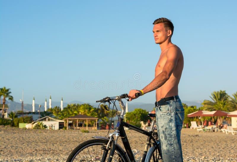 Homem novo com uma bicicleta que anda na praia no por do sol fotografia de stock royalty free