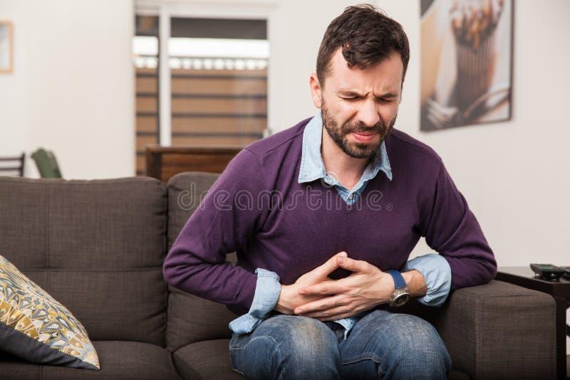 Homem novo com uma dor de estômago imagens de stock