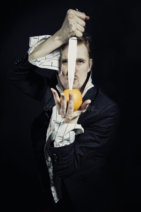 Homem novo com uma faca e uma laranja foto de stock royalty free