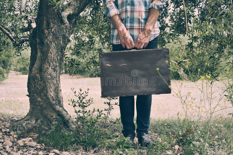 Homem novo com uma mala de viagem marrom velha em um cenário natural imagem de stock