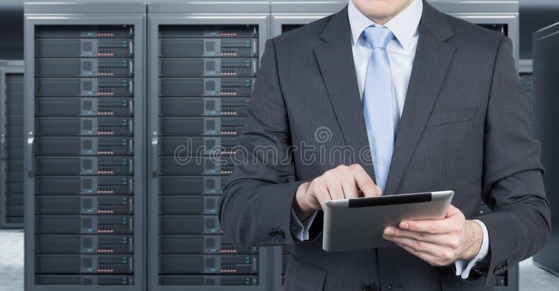Homem novo com uma tabuleta na frente do servidor para o armazenamento de dados  ilustração royalty free