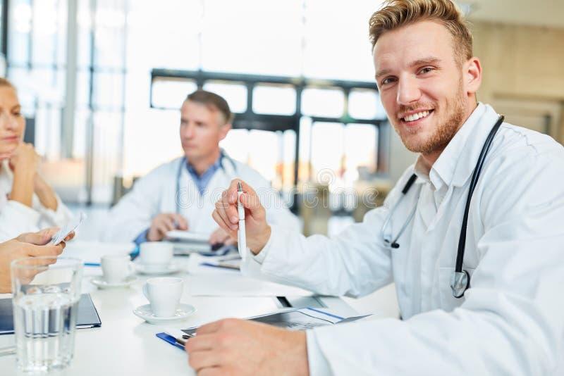 Homem novo como um assistente médico em uma oficina fotografia de stock