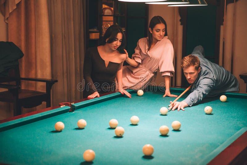 Homem novo concentrado do ruivo que aponta na bola de bilhar Olha direto A jovem mulher no vestido cor-de-rosa senta-se no bilhar imagens de stock royalty free