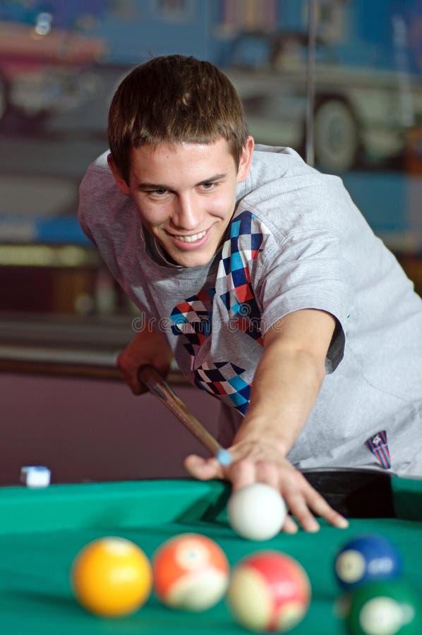 Homem novo concentrado que joga o snooker fotografia de stock royalty free