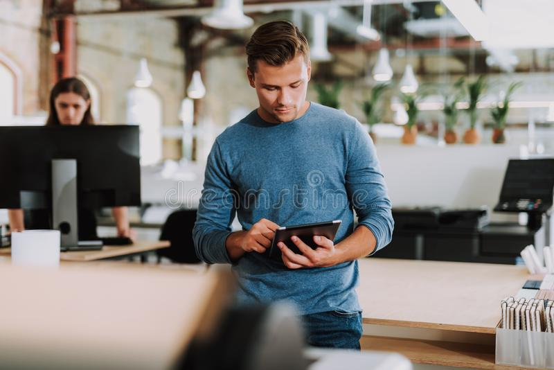 Homem novo concentrado que usa a tabuleta no escritório imagem de stock