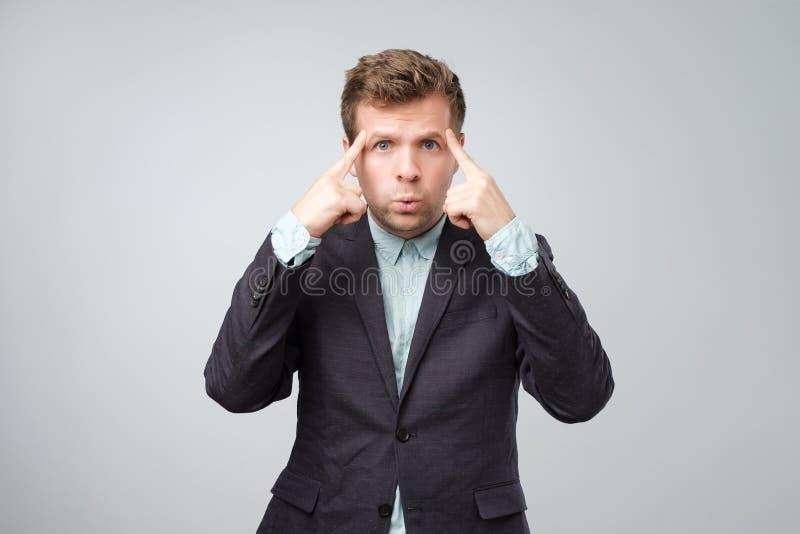 Homem novo confundido infeliz que aponta em sua cabeça com dedos e que olha a câmera fotos de stock