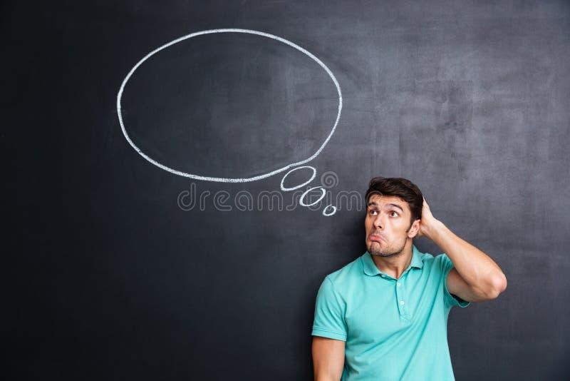 Homem novo confuso pensativo que está e que pensa sobre o fundo do quadro-negro imagens de stock