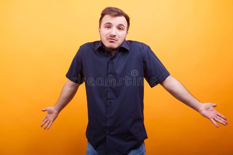 Homem novo confuso que aumenta seus ombros imagem de stock