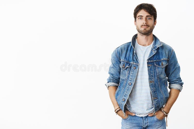 Homem novo considerável à moda e cofnident com barba e olhos azuis que mantêm as mãos em uns bolsos como estar contra o cinza imagens de stock
