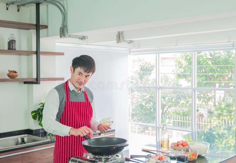 Homem novo considerável, asiático no avental vermelho Cozimento para o alimento na sala da cozinha em casa fotografia de stock royalty free
