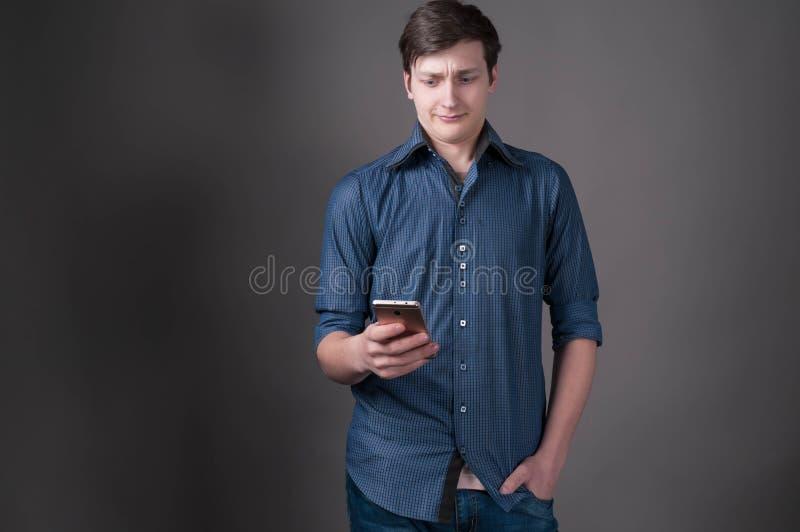 Homem novo considerável assustado na camisa azul com mão no bolso que olha o smartphone no fundo cinzento fotos de stock