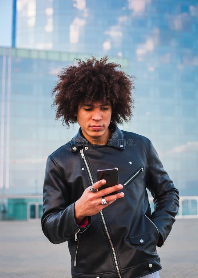 Homem novo considerável com cabelo afro usando um telefone esperto e olhando sério, fundo da cidade fotografia de stock