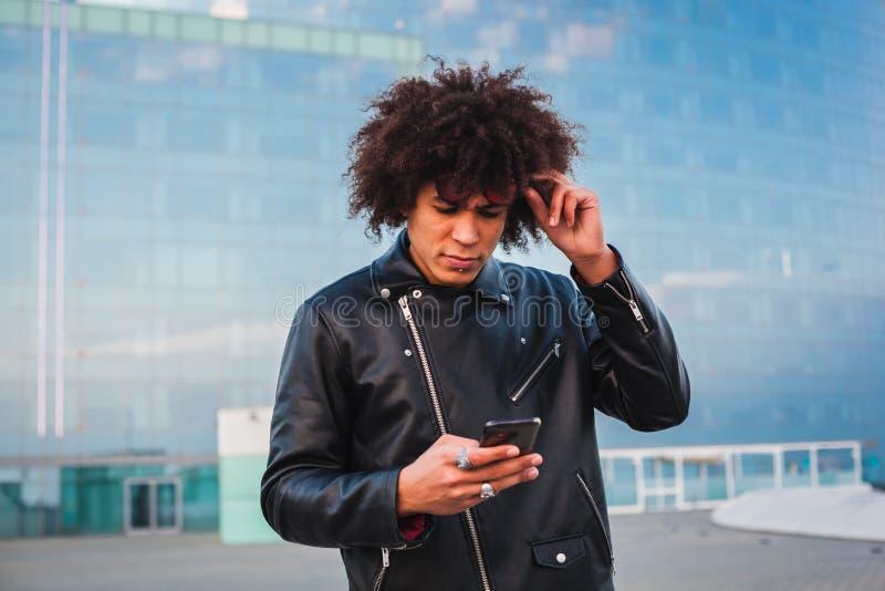 Homem novo considerável com cabelo afro usando um telefone esperto e olhando sério, fundo da cidade fotos de stock